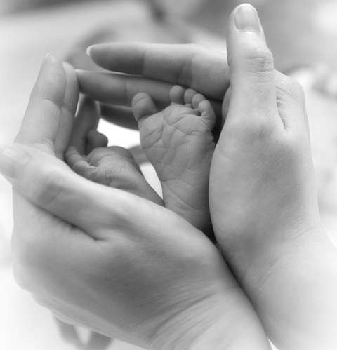 The feet of a child and the hands of a woman