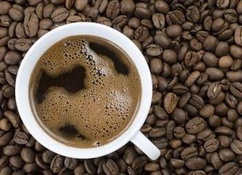 Roasted coffee beans and brewed cup of coffee