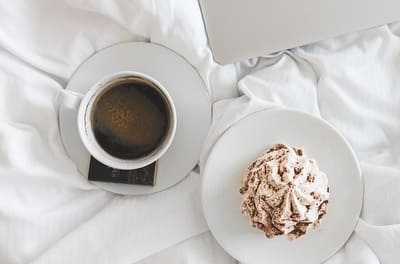 Cup of coffee with cake on the bed